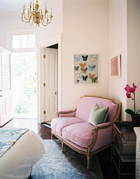 A vintage pink loveseat gets a little bit of edge with contrasting black piping.
