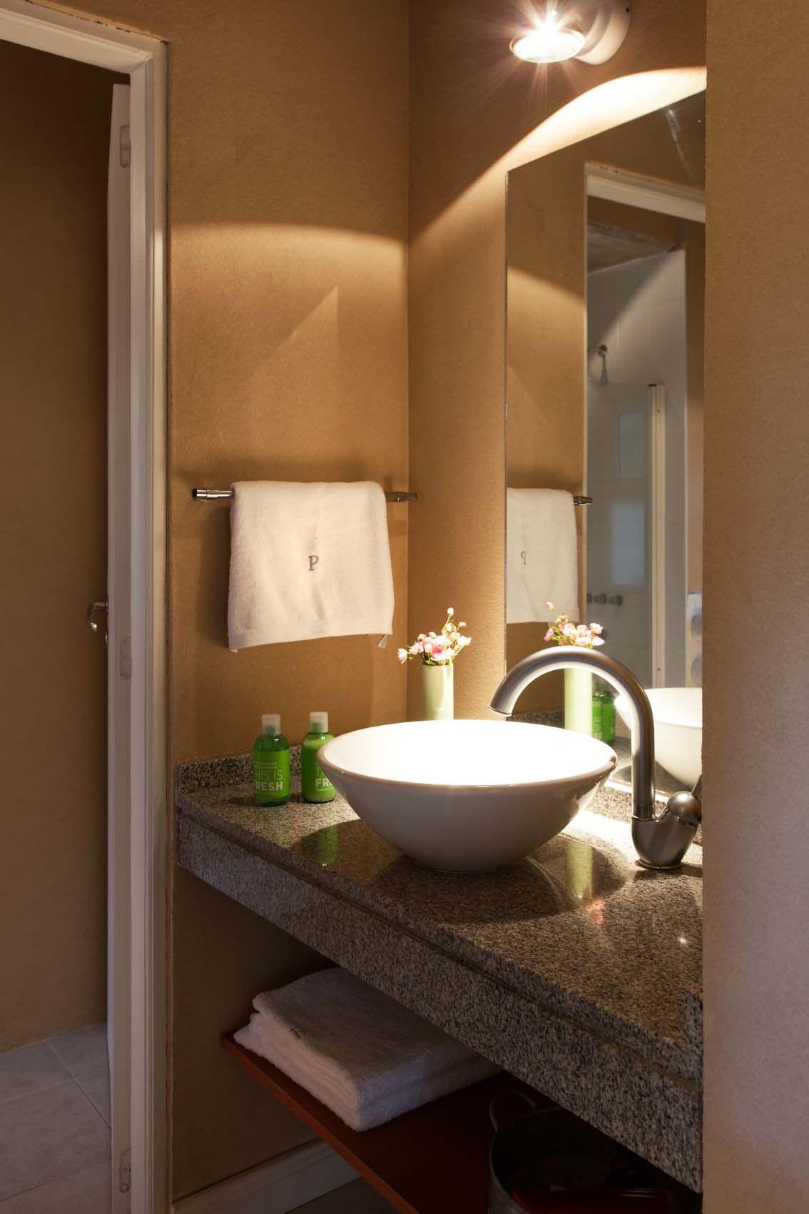 Baño súper coqueto y minimalista del Hotel Plenilunio. Bacha de cerámica blanca sobre mesada símil mármol, grifería moderna en color metálico, paredes pintadas de marrón y luminaria con luz focal.