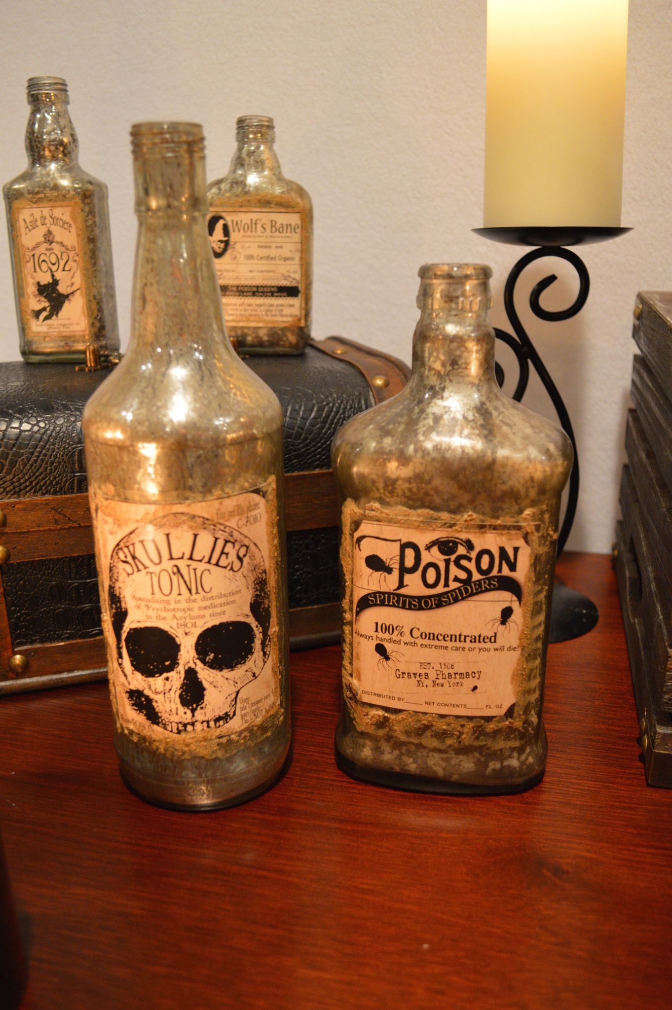 Antique Halloween Bottles (Large) - Bethany Lowe – Black Bow Halloween Shoppe. Keep your secret potions safe in these beautiful vintage bottles.  Your Spirits of Spiders and Skullies Tonic can be paired with the Antique Halloween Bottles (Small) or Antique Halloween Bottles (Medium) to create a creepy collection!  Sold as a set of 2 bottles.  Bethany Lowe. Glass with printed paper labels.  11 1/4″ x 8 3/4″.  FREE SHIPPING!