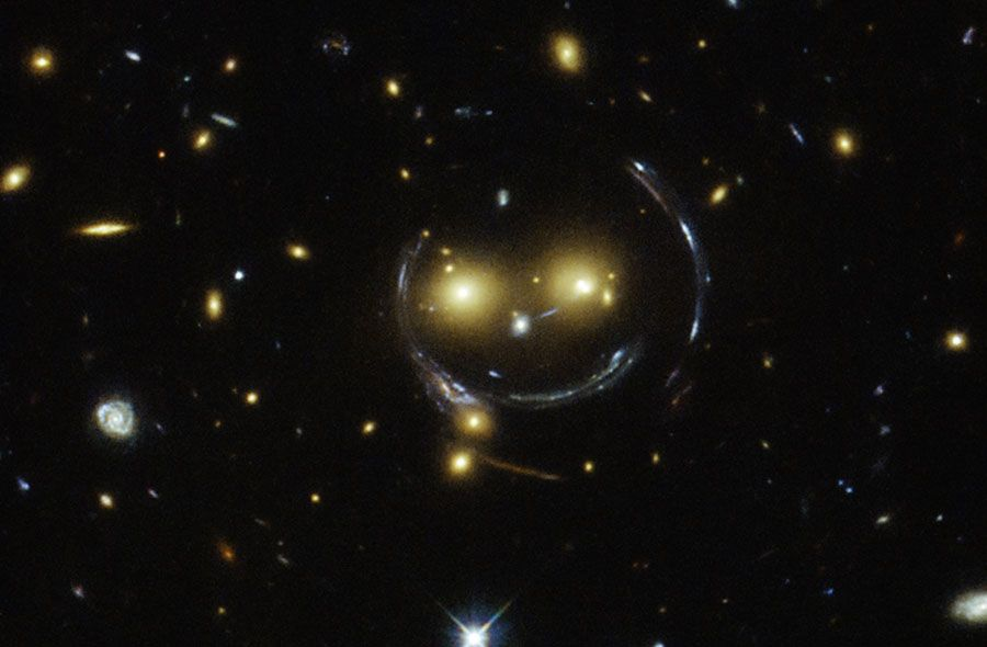 """A galactic smile. In the center of this Hubble image are two faint galaxies that seem to be smiling. You can make out two orange eyes and a white button nose. In the case of this """"happy face,"""" the two eyes are the galaxies SDSSCGB 8842.3 and SDSSCGB 8842.4, and the misleading smile lines are actually arcs caused by an effect known as strong gravitational lensing, distorting light from more distant objects."""