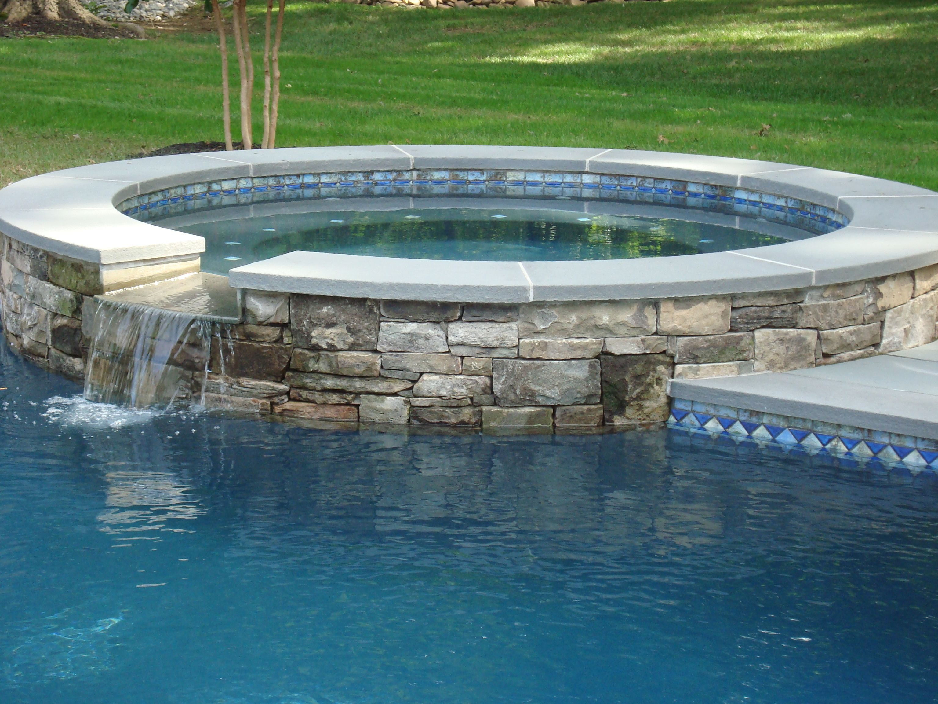 Custom stacked stone raised spa with blue stone coping and for Raised pool designs