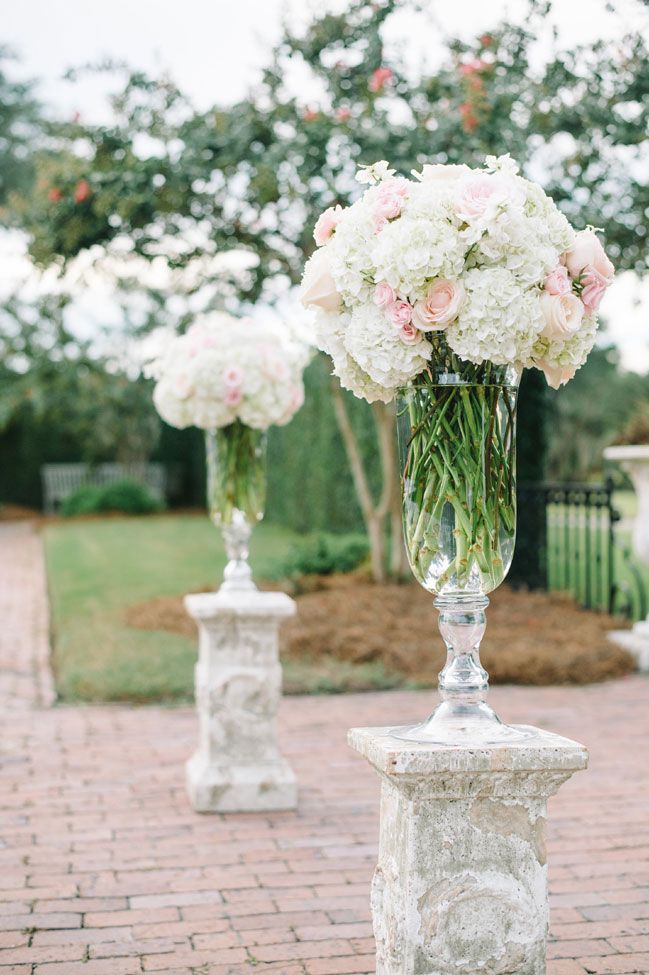 Tall Vases filled with white and pale pink blooms at the ceremony   Classic Southern Charleston Wedding At Dunes West Golf & River Club   Photograph by Aaron and Jillian Photography http://storyboardwedding.com/southern-charleston-wedding-dunes-west-golf-river-club/