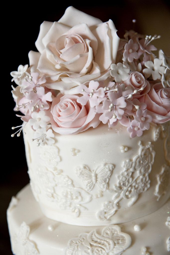 Close up of sugar flowers and lace on cake.