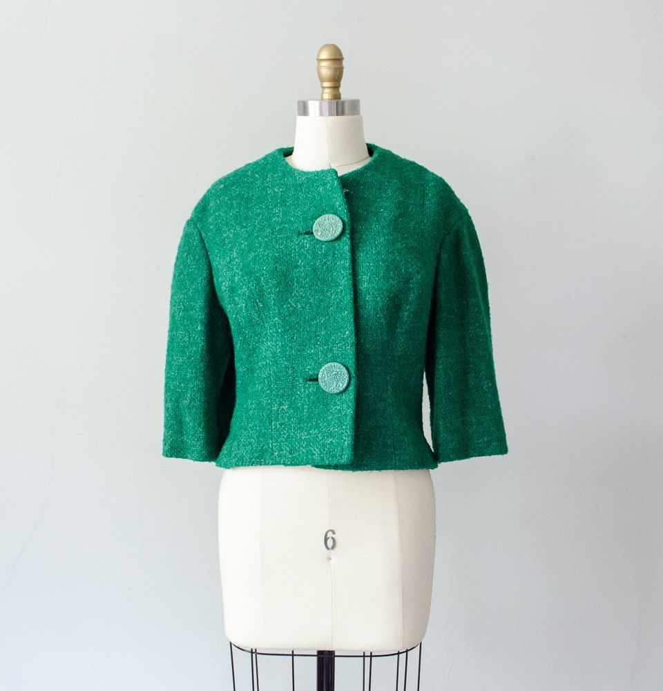 A vibrant cropped jacket made from bouclé wool in grass green with white flecks. Large round buttons secure at the front, with an extra snap at the neck. 3/4 length sleeves and darting at the waist. Fully lined in rayon crepe.  Size: medium Bust: 38 Waist: 36 Length: 20 Shoulders: 16  Condition: Very good; this may be a homemade piece, as there is slight unevenness on the two sides. This can be seen best at the hem in the second photo.
