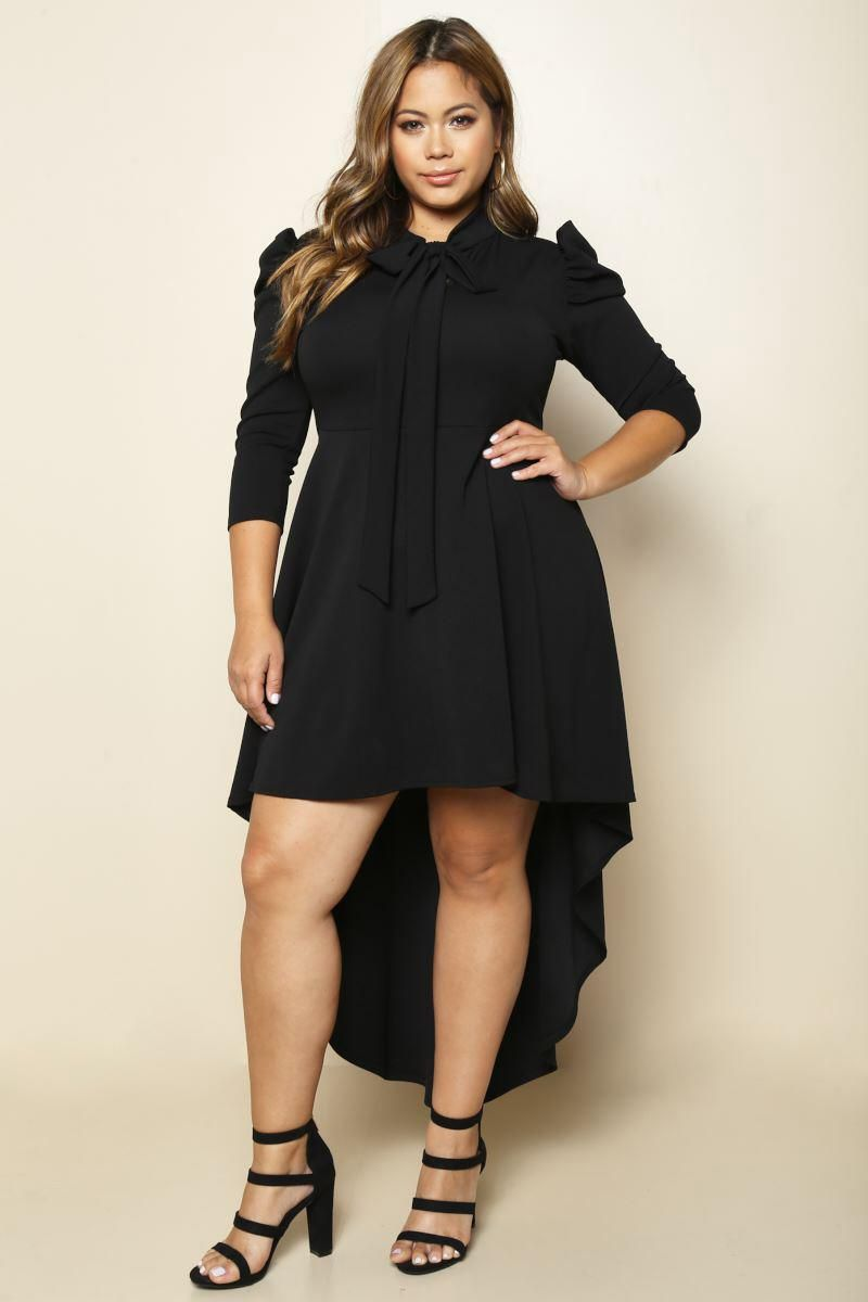 8f91813a437 A plus size maxi dress with a bowed neckline and 3 4 sleeves. Features  puffed shoulders. Solid colored all over and a flared hi-lo hem.