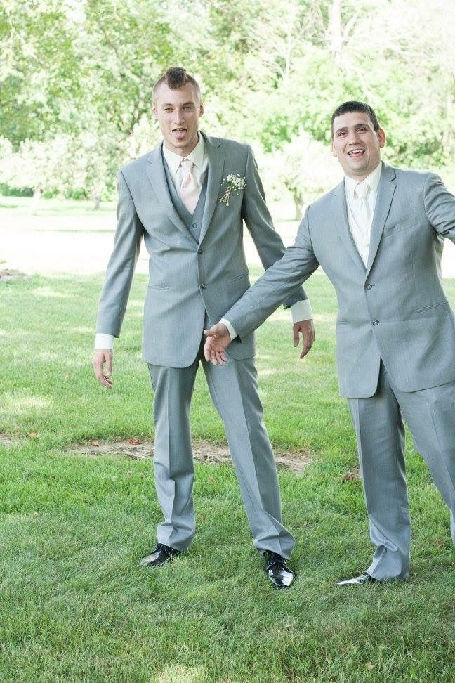 Funny groom and groomsman pose for outdoor wedding photo. Suit ...