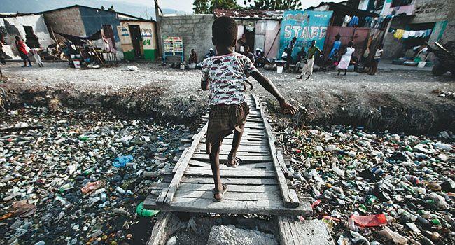 Miseria Um Menino Atravessa Corrego Cheio De Lixo Em Cite Soleil