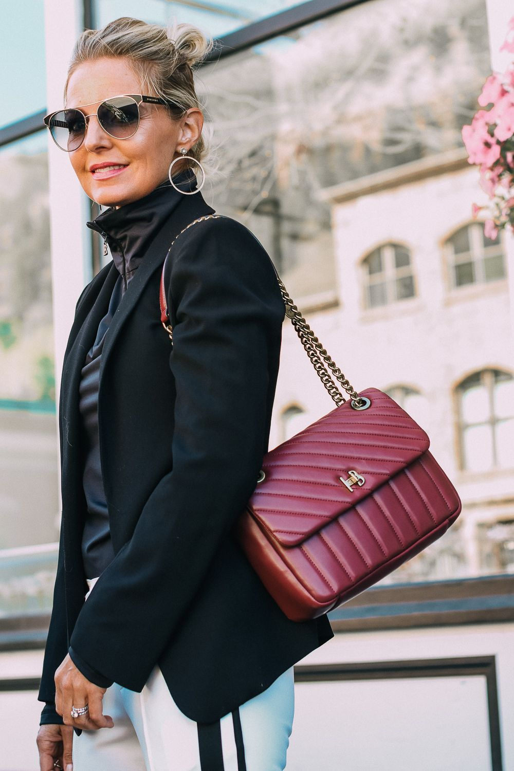 Henri Bendel quilted crossbody bag in burgundy with gold chain link detail  paired with Pam   Gela striped pants, Bogner turtleneck and black blazer 9779779982