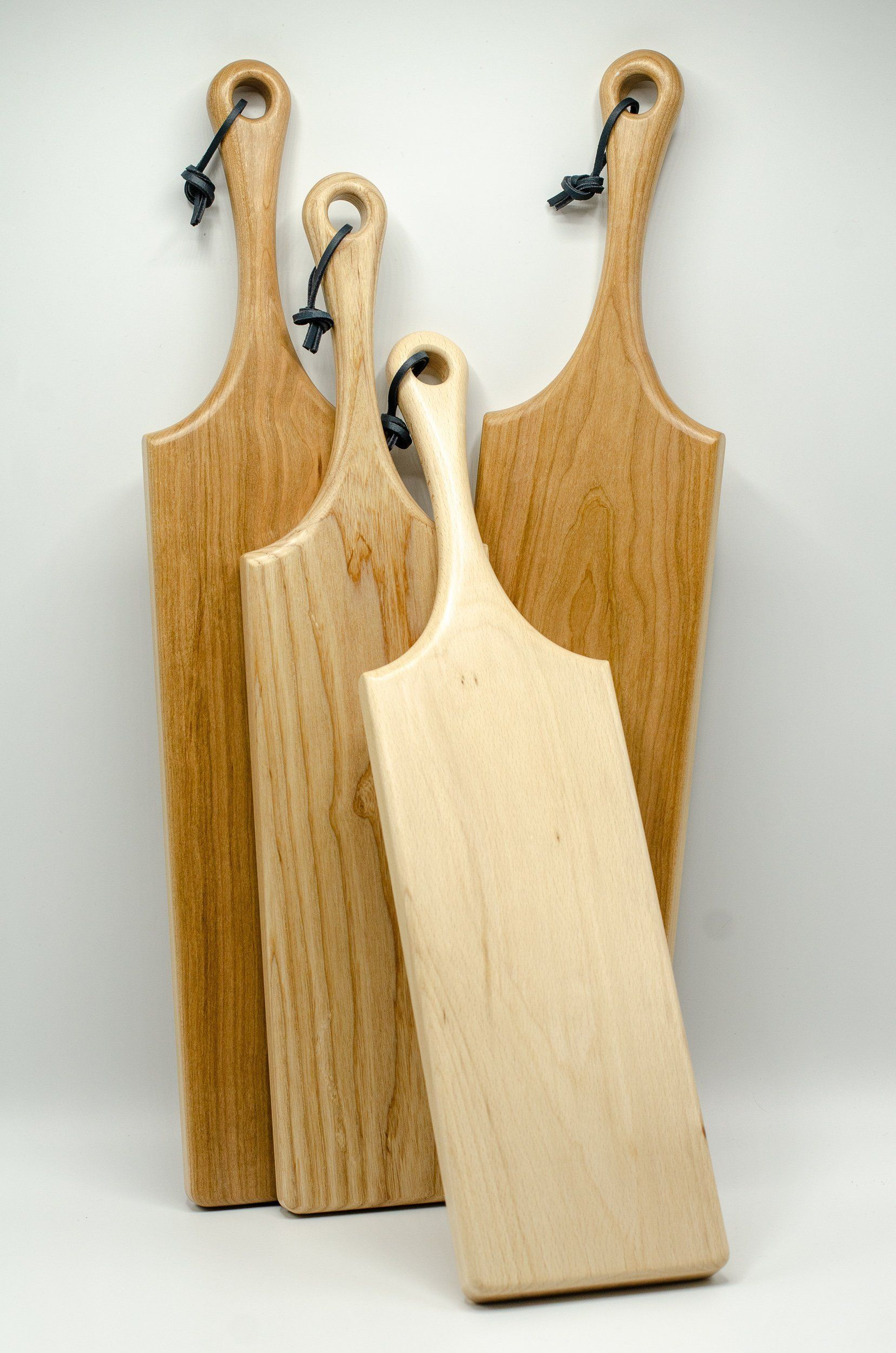 Wooden Cutting Board, Wooden Chopping Board, Charcuterie Board, Wood Serving Board, handmade in London, perfect gift for foodies is part of Wooden Home Accessories Cutting Boards - Elegantly carved solid wood serving boards with a multitude of uses   Each board features an ergonomic curved handle to make carrying it a pleasure  The boards are all designed, produced and handfinished by me in my small workshop in the heart of London   Each board is unique due to the size and grain pattern   Current stock features cherry, ash and beech, and each is finished with a navy leather loop for hanging    All boards are finished with my own recipe foodsafe conditioning wax, which will nourish and protect your board  Perfect as an anniversary or Christmas present   Feel free to express a preference if you like a particular board and I will accommodate where I can  Uses Cheese board Chopping board Serving platter Display board Cake board Dimensions Width 18cm Thickness 2cm Length 58cm (cherry), 53cm (ash), 51cm ( beech) Hardwood is a natural product, and as such there will be variations in colouring, grain patterns and markings   This makes each board unique and is part of the charm of owning handcrafted solid wood furniture and accessories
