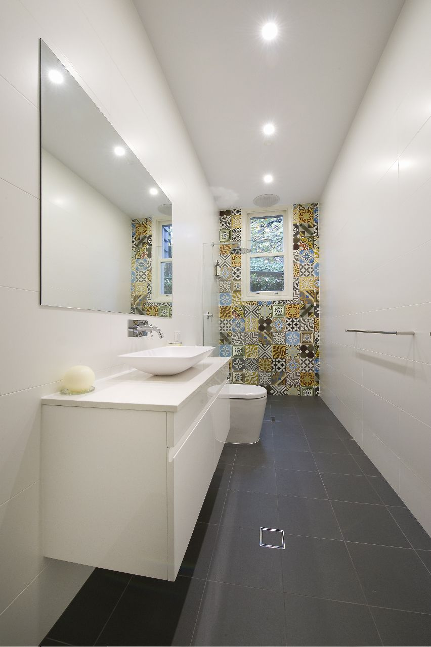 Long narrow bathroom with tiled feature wall around the - Narrow toilets for small bathrooms ...