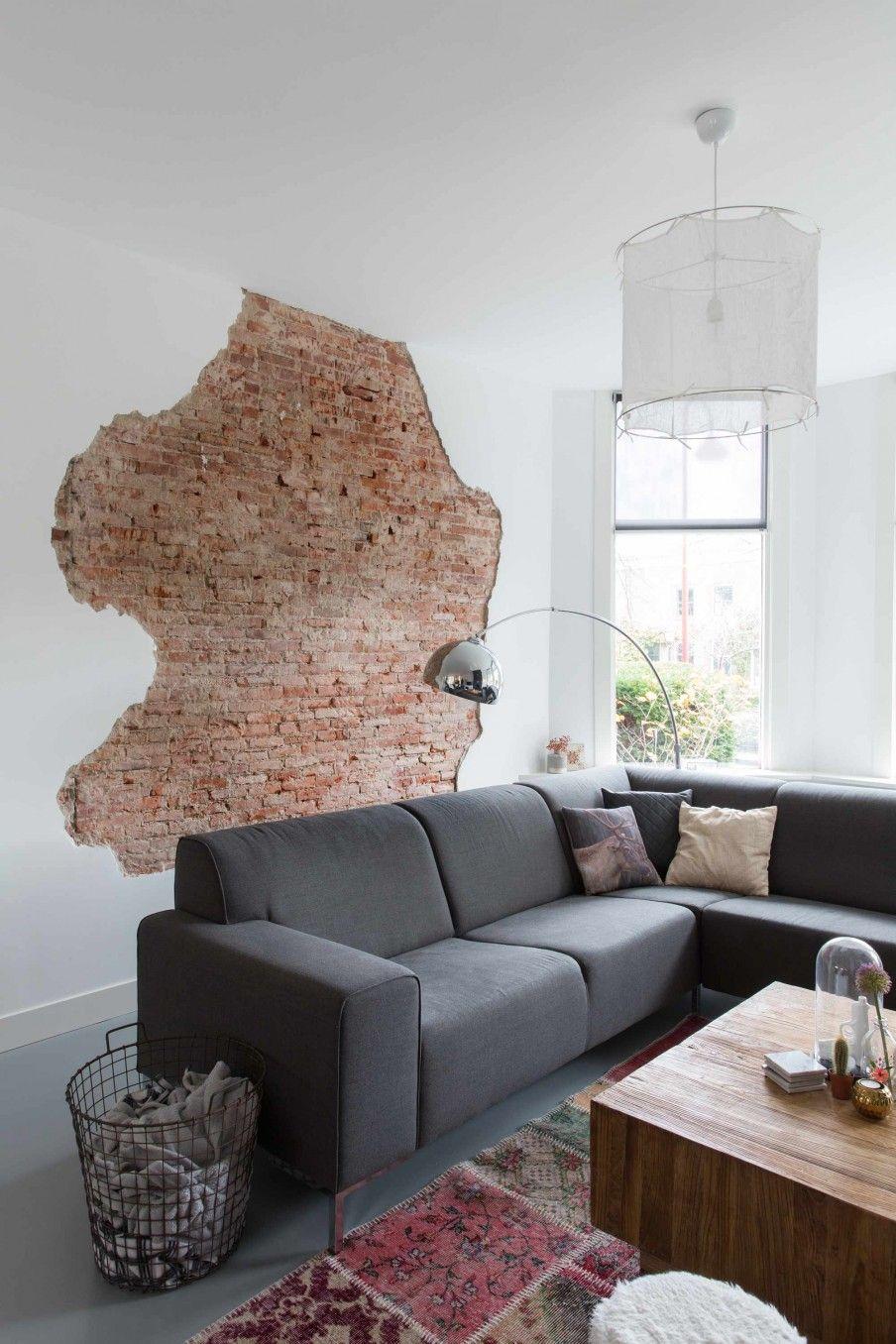 Woonkamer met grijze bank en bakstenen muur  Living room