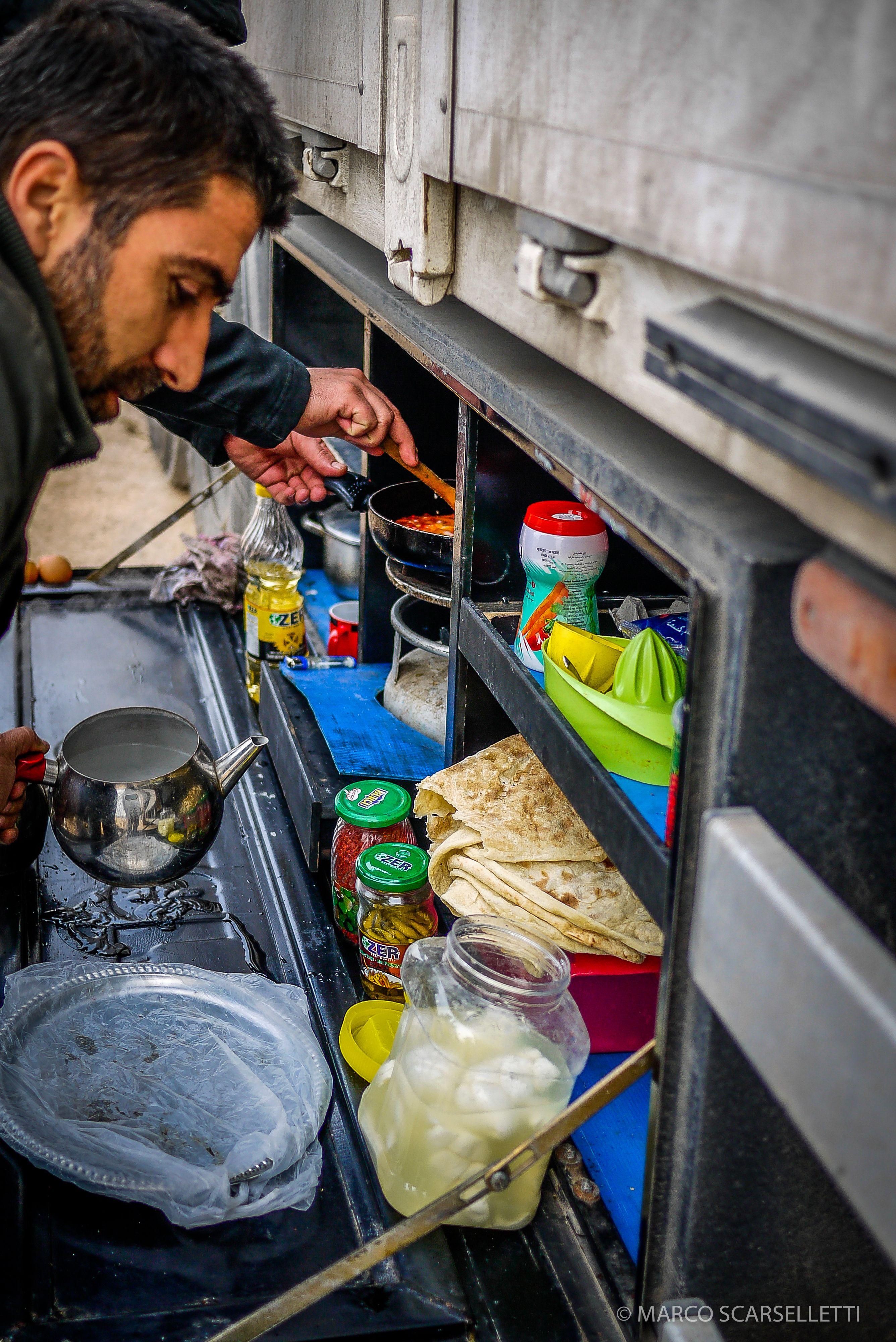 Camionisti turchi che preparano il pranzo nella loro cucina portatile inserita nel camion