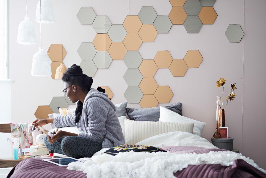 Billede af soveværelse med mønster lavet af kobber- og sølvfarvede spejle på væggen over sengen.