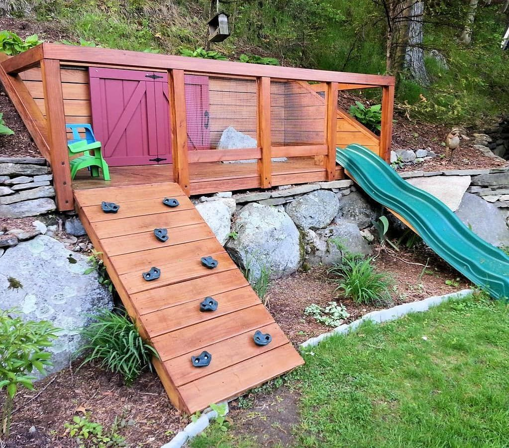 42 Kids Playhouses That Are Cooler Than Your Real 1 Sloped Backyard Playground Landscaping Backyard Playground Diy backyard hill slide
