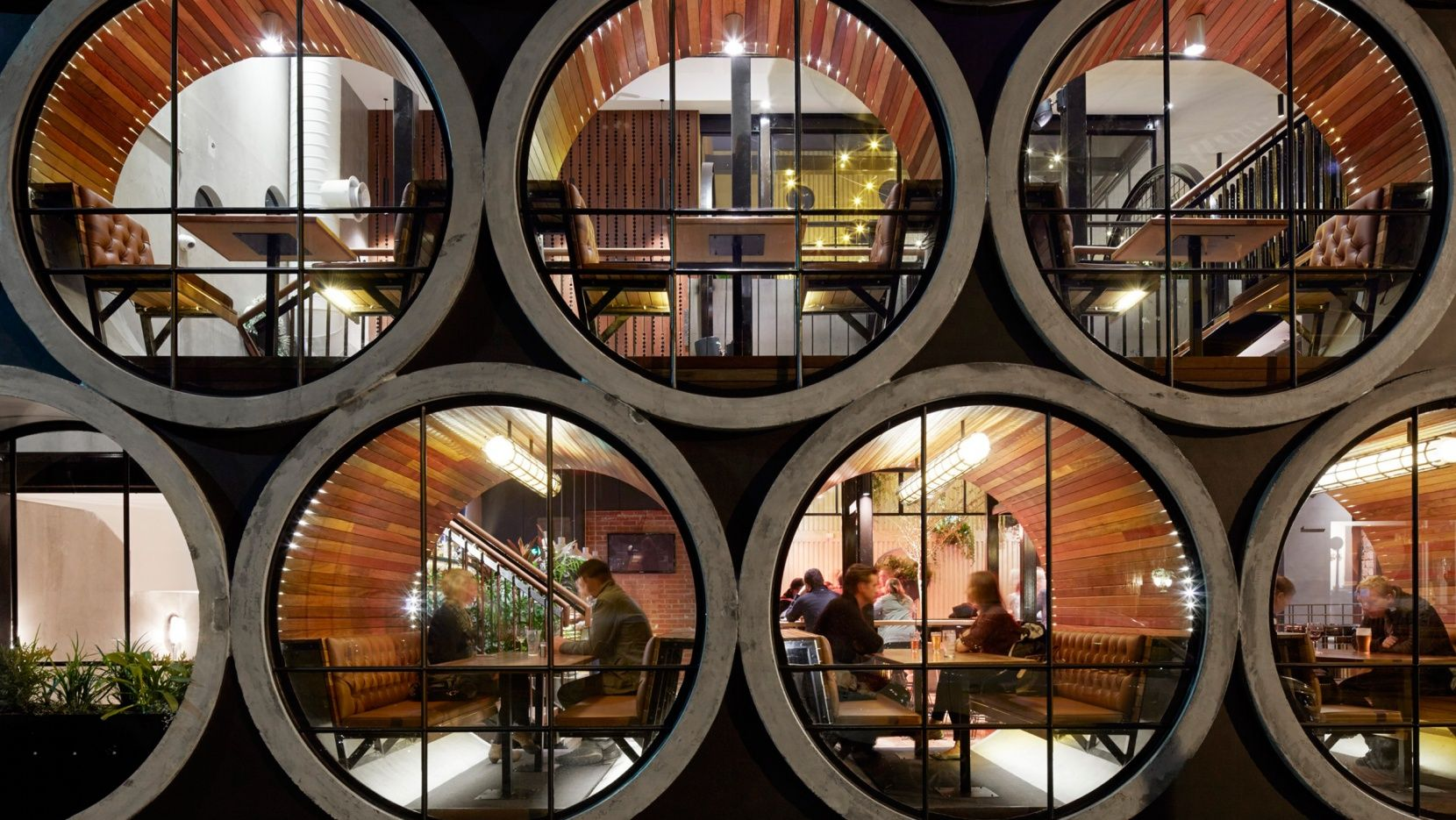 Using concrete pipes to create multi-level booth seating, the Prahran Hotel by Techné Architects in Melbourne, Australia, is a pub that offers its patrons the chance to sit snugly right inside its façade.