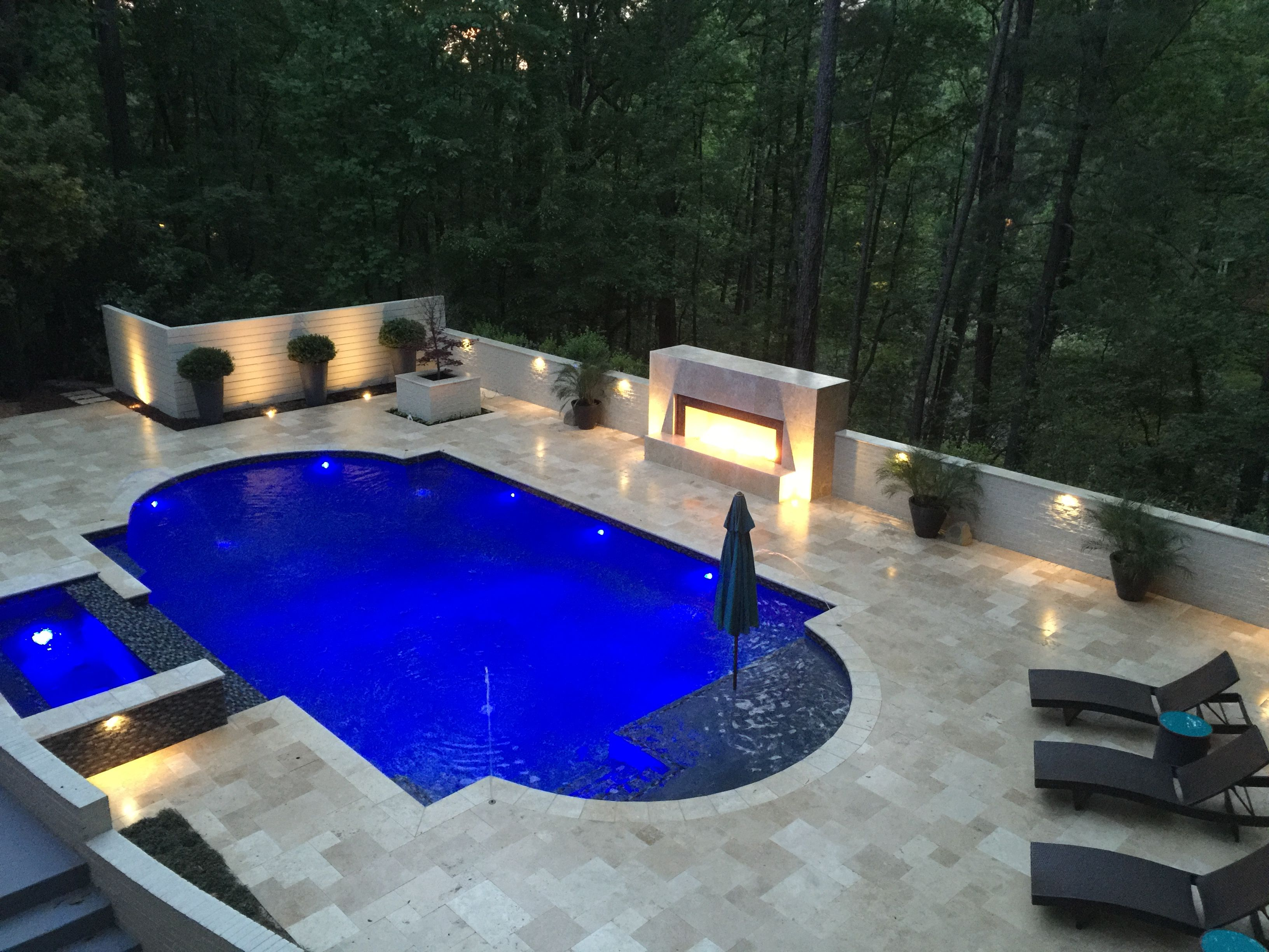 Grecian shaped gunite swimming pool with a spillover spa for Pool design with tanning ledge