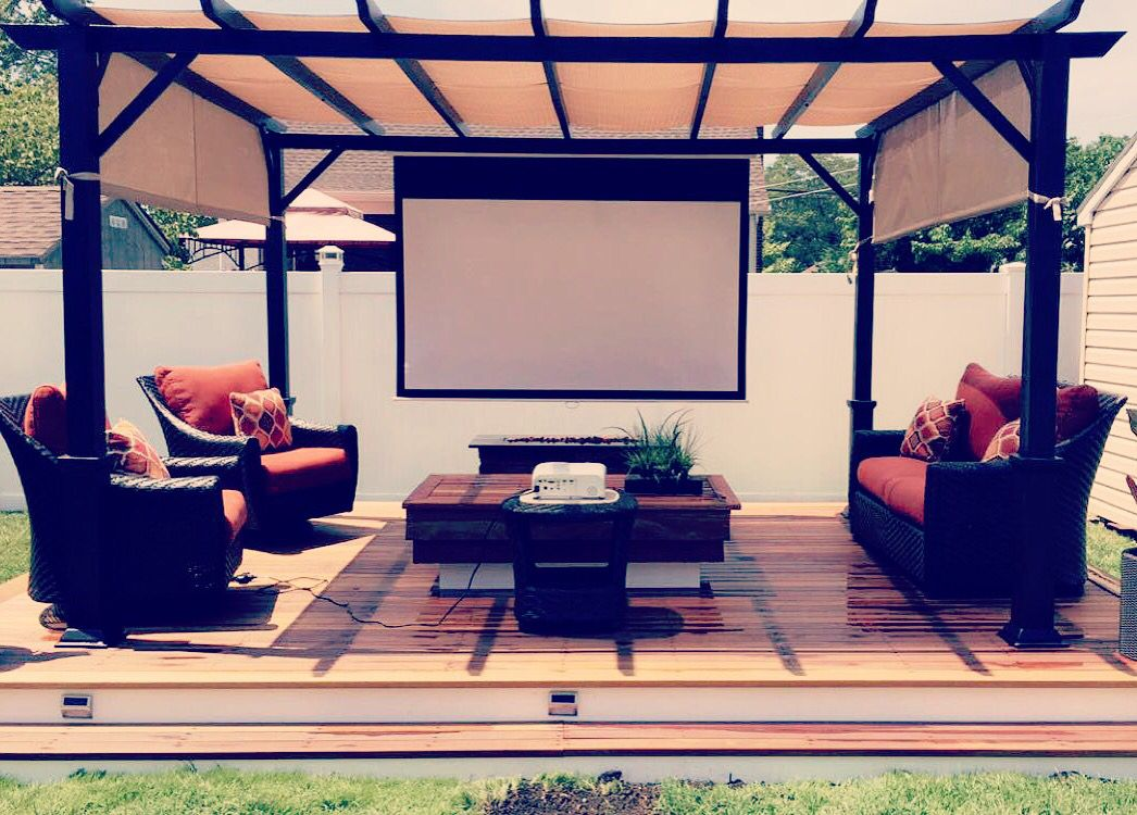Outdoor Relaxation. Ground level deck. Patio furniture. Outdoor projector.
