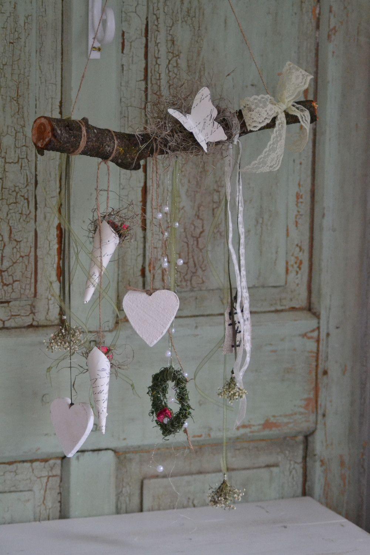 An einem derben Ast hängen Kränzchen, Herzen, Rose – Ostern Dekoration Garten Beton