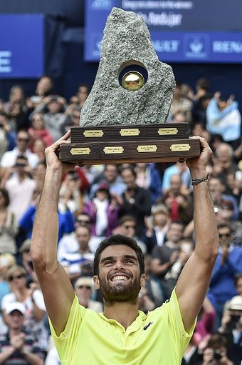 Pablo Andujar of Spain, celebrates with the trophy after he won the final match against Juan Monaco of Argentina at the Swiss Open tennis tournament in Gstaad, Switzerland, Sunday, July 27, 2014. (AP)