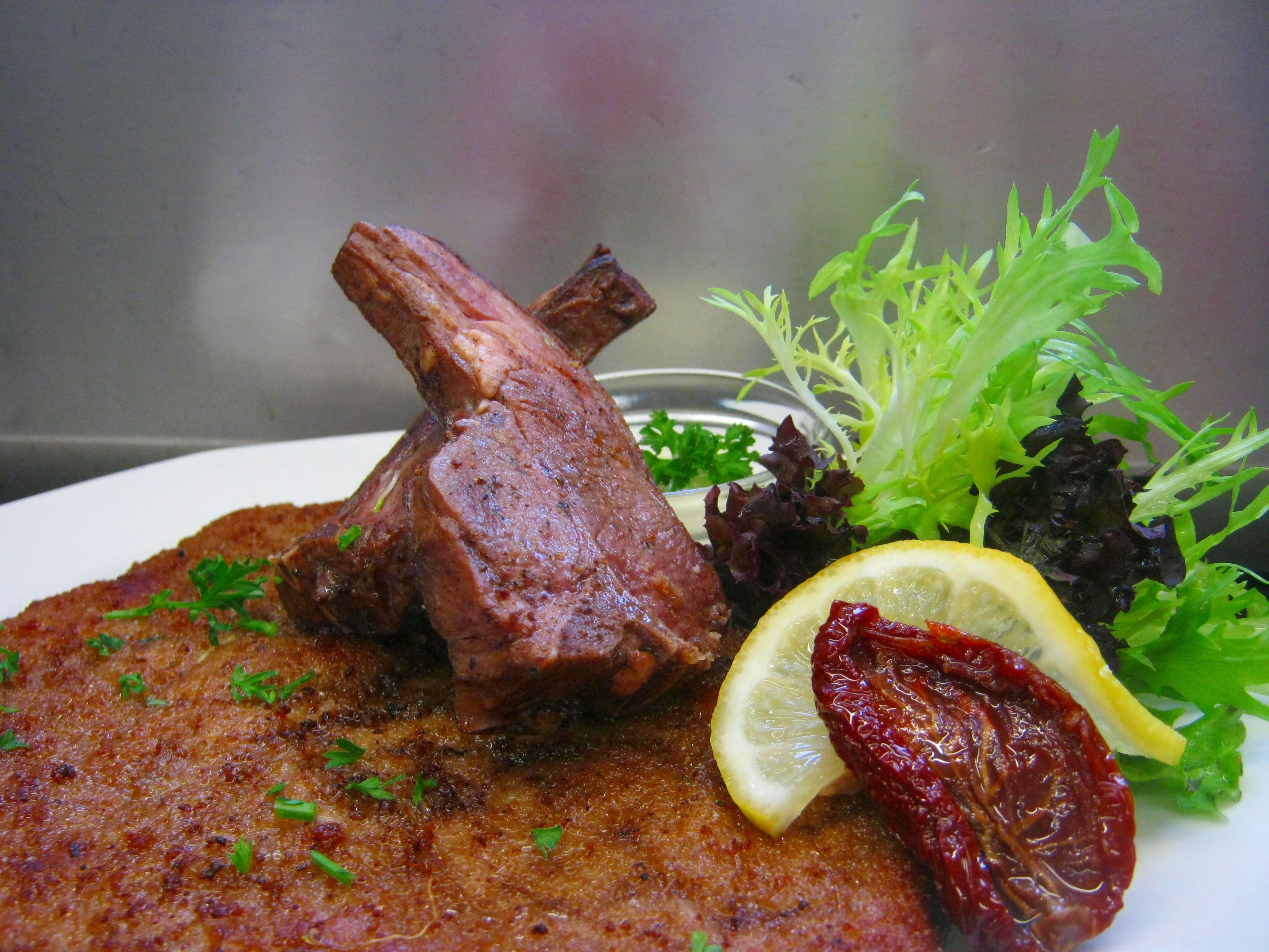 De schnitzel van de maand Oktober: een  heerlijke schnitzel met  2 lamskoteletten en een aioli saus.