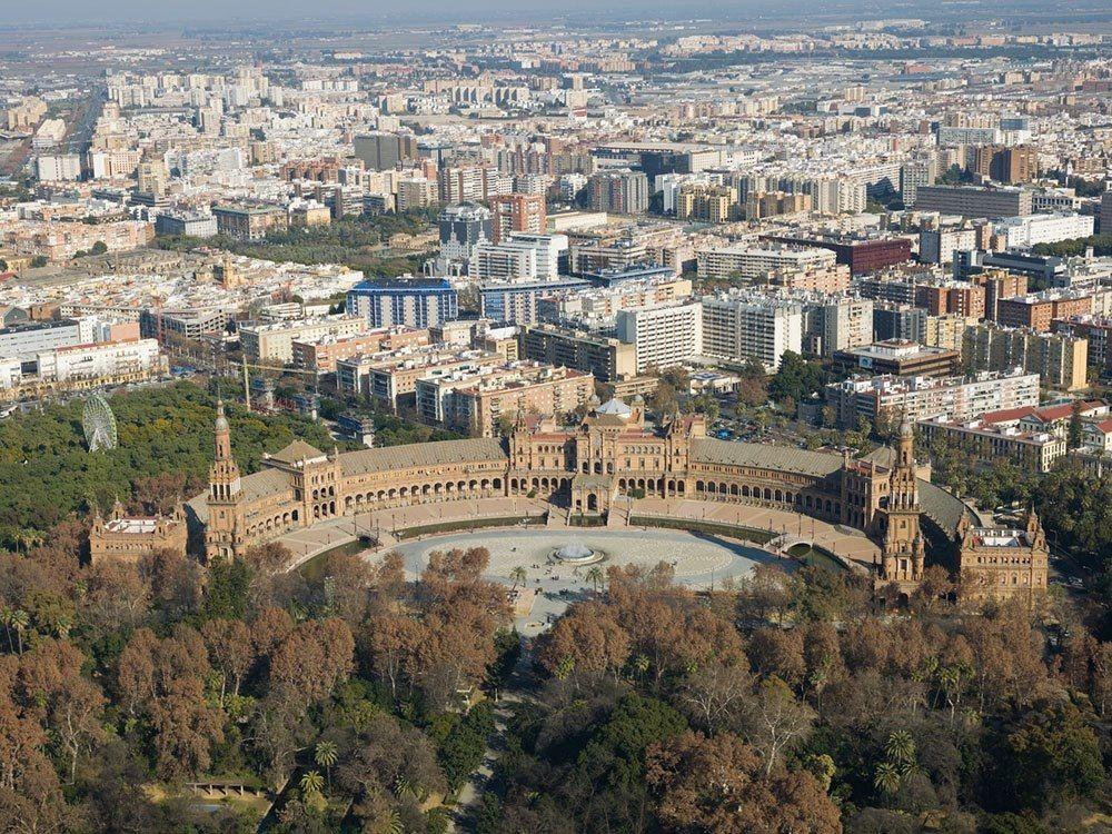 Plaza España ( Sevilla )  la plaza es de grandes dimensiones ( 200 metros de diámetro, 50,000 metros cuadrados aproximadamente ), tiene una forma semieliptica, que simboliza el abrazo de España .