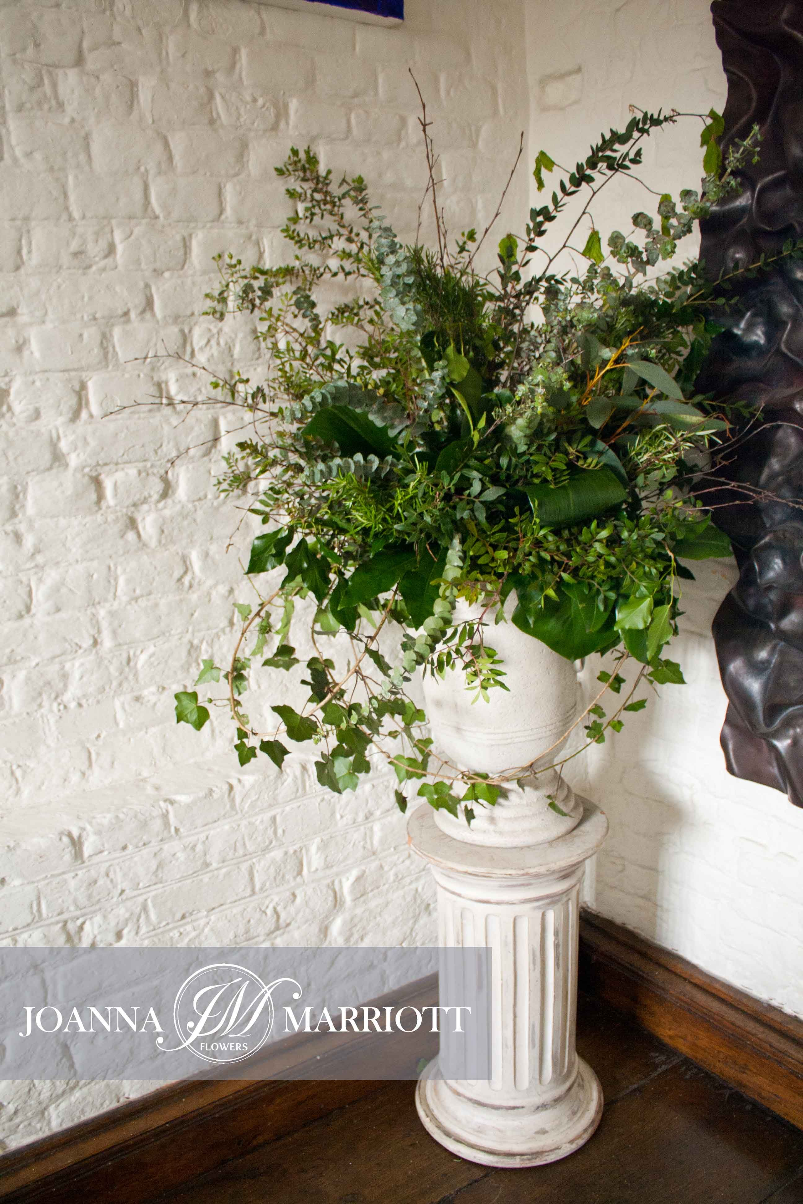 Green Pedestal Arrangement Composed Of Variety Of Foliage
