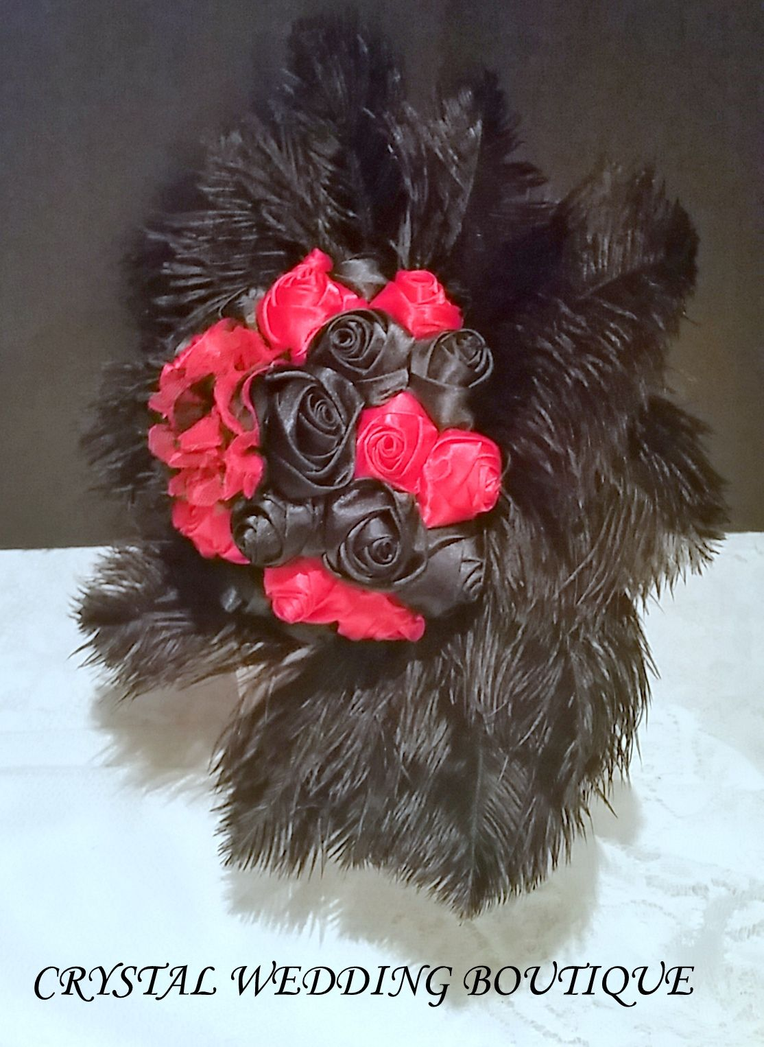 Red and black satin rolled roses with chiffon flowers surrounded by ostrich feathers