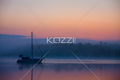 colourful sunset - The sun setting creates vibrant colours with a sailboat in the foreground.