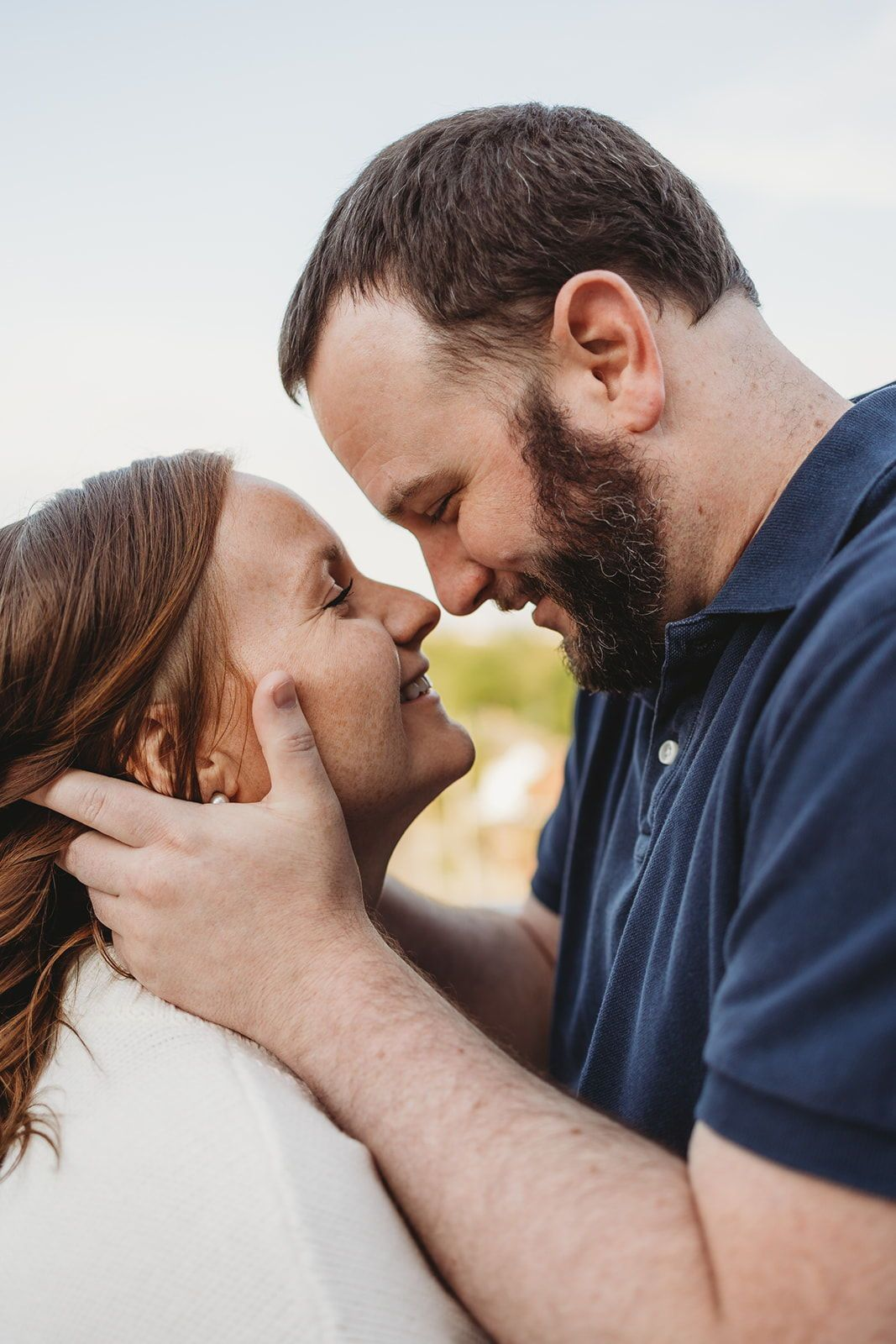 Cute engagement session at western michigan university in park. Perfect inspiration for couples photo shoot poses ideas. Fiance holding girls face about to kiss. Engagement photo shoot inspiration in fall! Traveling Wedding and Couples Photographer. Lindsay Elaine Photography.