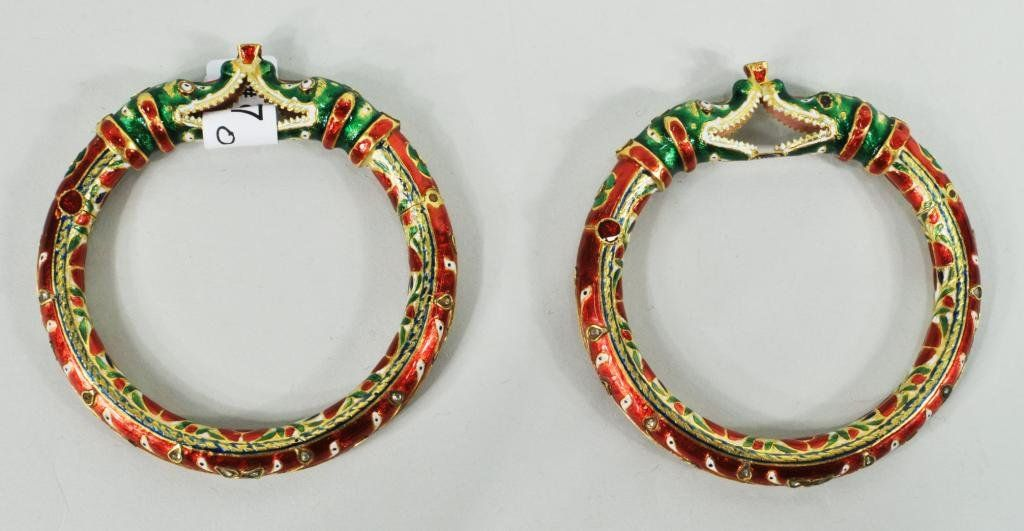 "Pair of Indian Mughal style 20K gold, foil backed diamond and enamel bracelets, 1st half of 20th C., with pair of green crocodile heads supporting a single diamond, wearing red enamel and diamond collars, bracelet length with foliate design inset with small diamonds, with closure secured by red enamel screw. Maker's mark in black enamel under lower jaw. Inner circumference approximately 6 1/2"". Two gold marks at hinge, gross weights 32.5 dwt and 33.3 dwt"