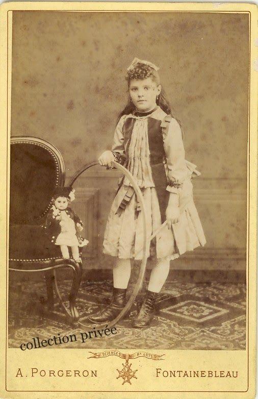 Jeune fille avec un cerceau et une poupée.  Photographie Adolphe Forgeron, 10 rue des Bois,  Fontainebleau, France circa 1885
