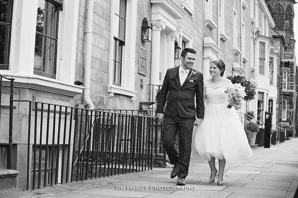 Bride and groom walking past Hotel du Vin in Harrogate