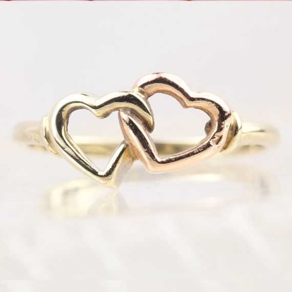 This ring has two entwined heart outlines one in yellow gold and