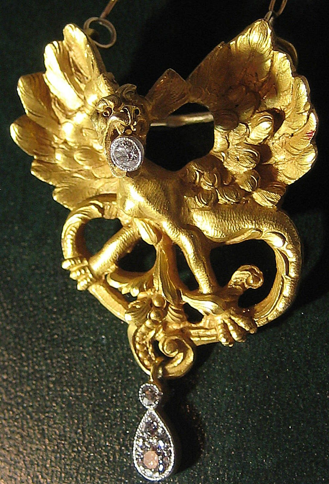 Amazing Art Nouveau pendant necklace at The Antique Guild in Old Town Alexandria, Virginia.   The gold pendant is in the shape of a rearing dragon holding diamonds in its mouth and with its tail. Via Diamonds in the Library.