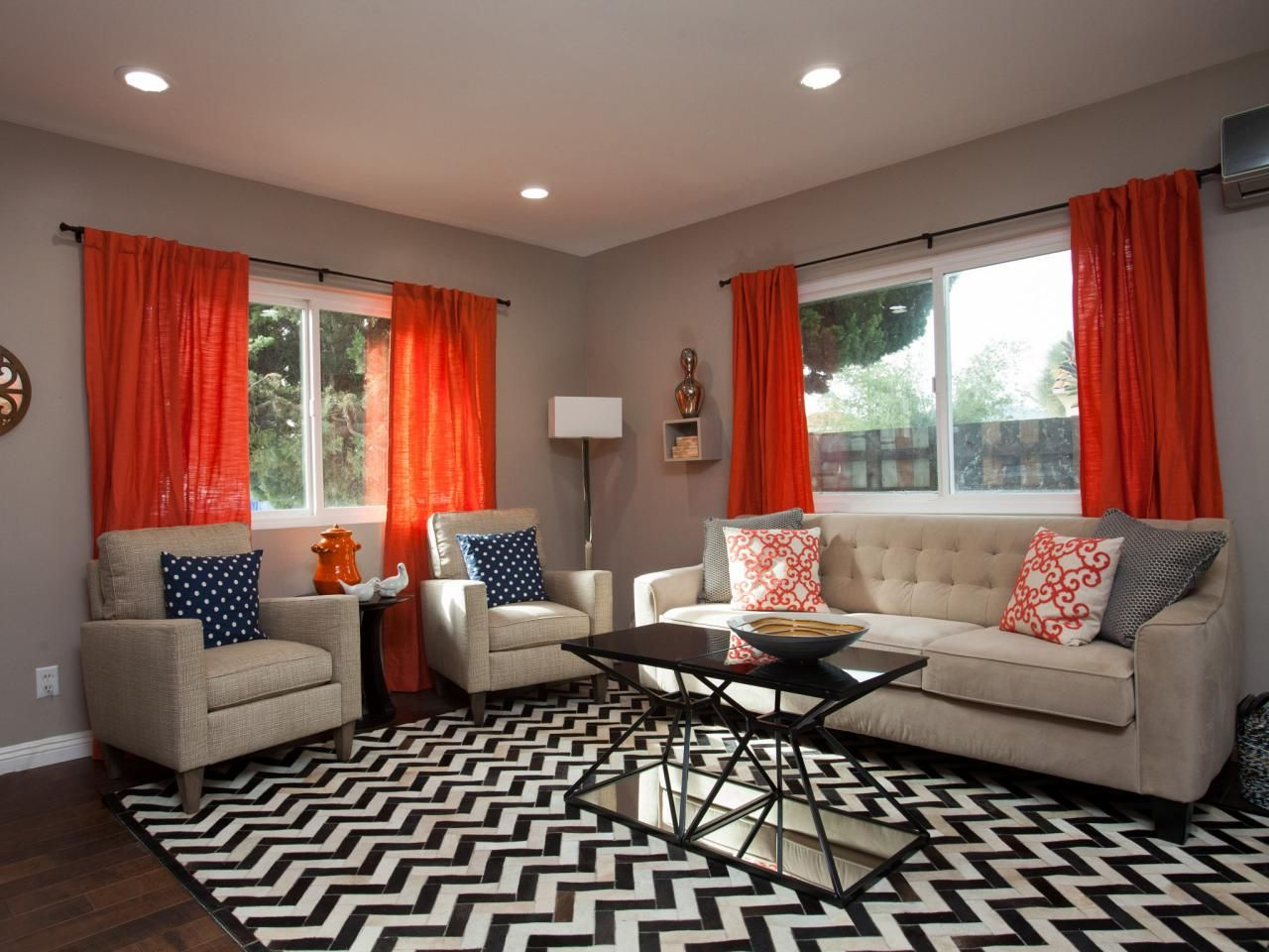 A Blackandwhite Chevron Rug Grounds The Living Room Seating Area Beauteous Orange Curtains For Living Room Inspiration