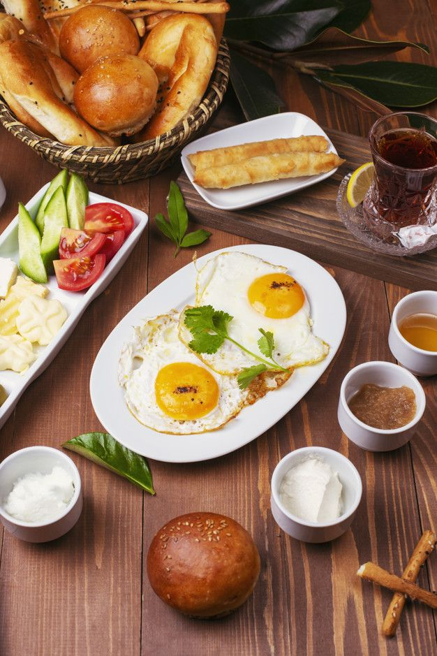 Download Turkish Breakfast With Fried Eggs, Tomato, Cucumber, Cheese Varieties, Black Green Olives, Honey, Jam, Cream Cheese, Galeta Bread And Glass Of Tea for free