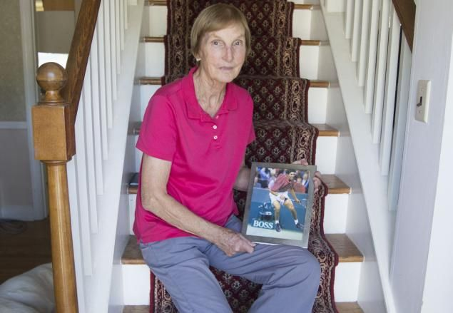 Betty Blake poses with a photo of her son James during a tennis match.(links to an article she wrote about raising black sons)