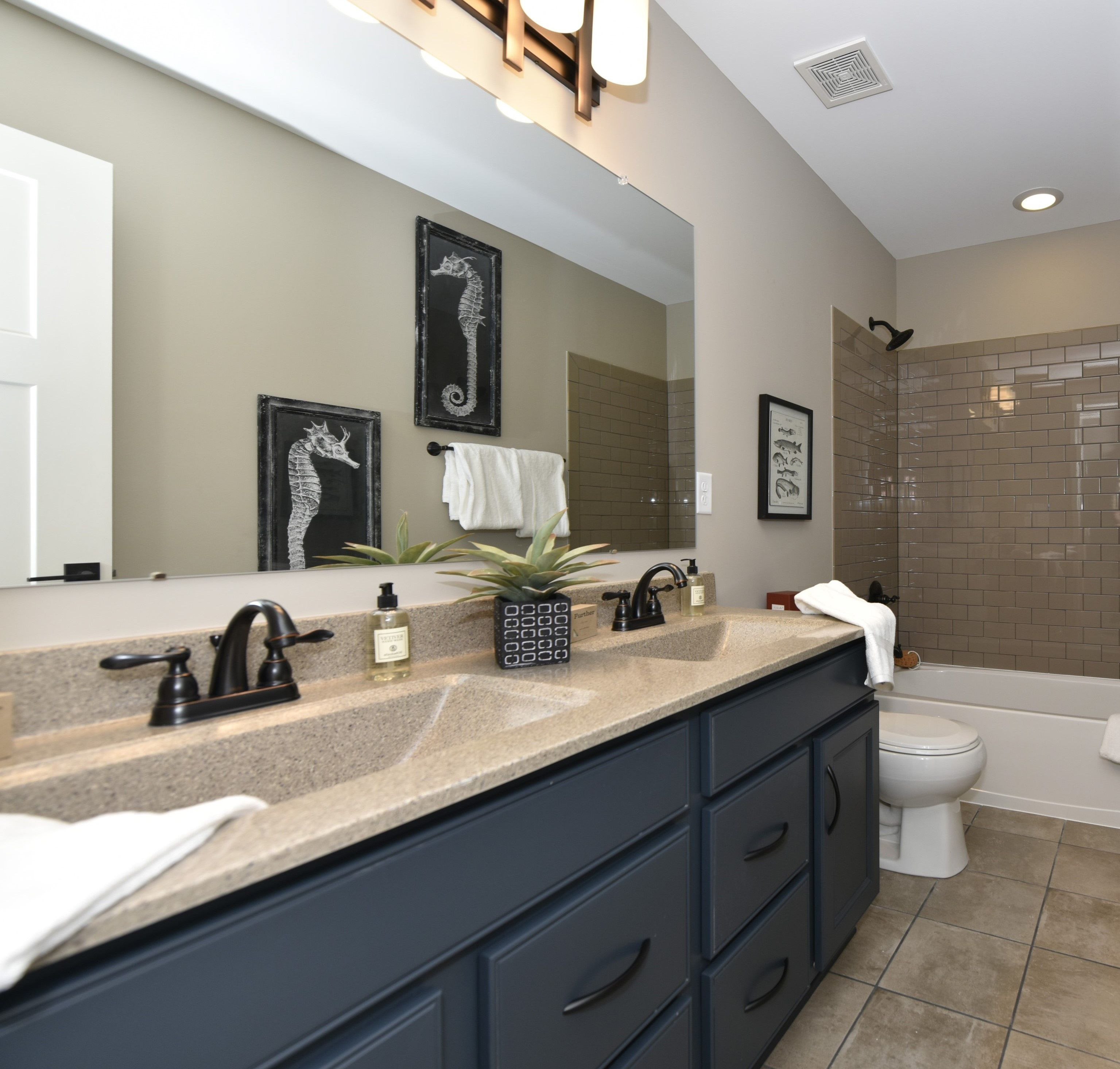 Square double sinks, subway tile, and gray cabinets make ...
