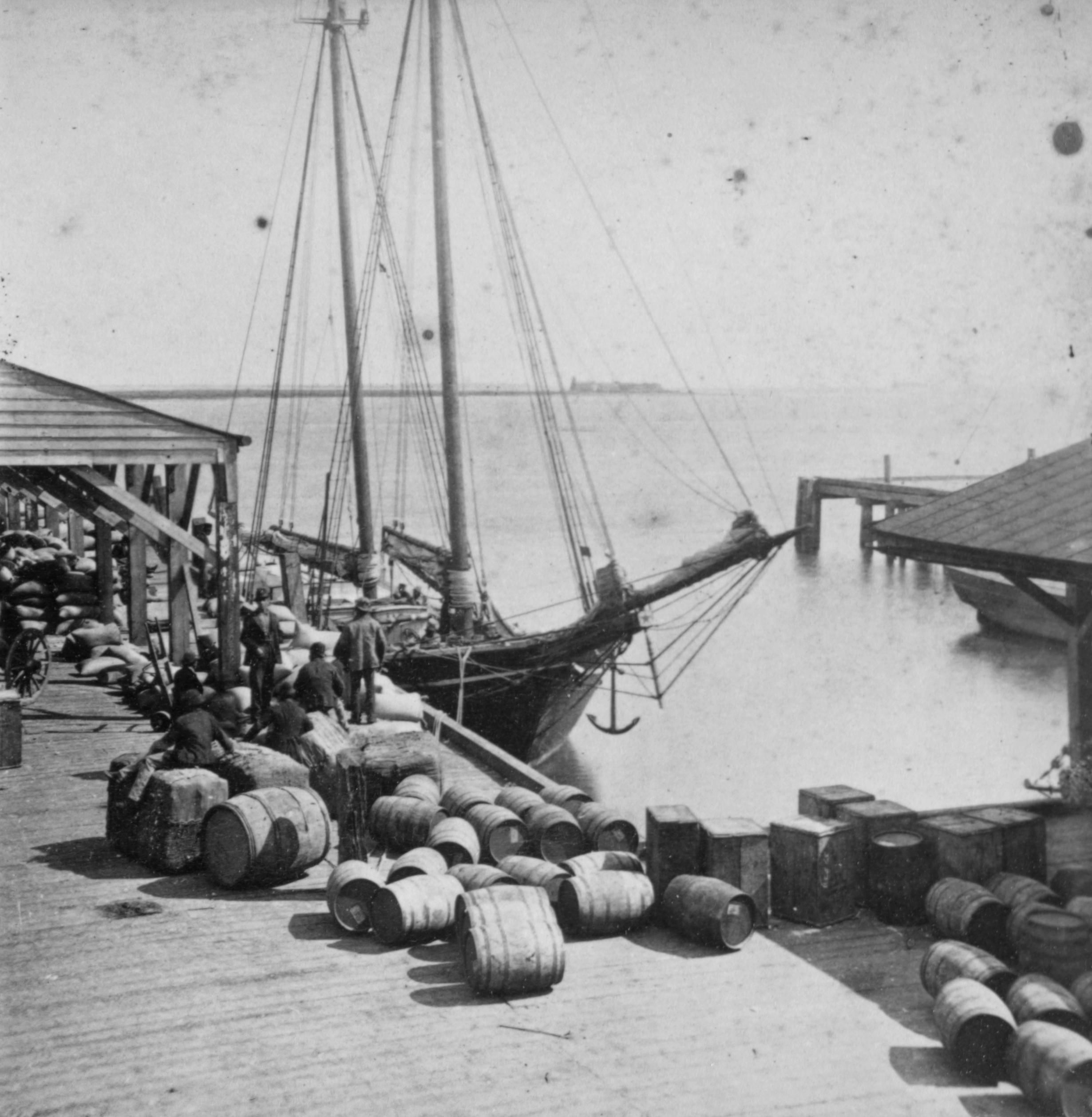 Click this image to show the full-size version. Supply ship at dock in Charleston Harbor. George L. Cook photographer who was evacuated from Charleston before it fell to the Union. Could this be a resupply boat for Sumter or a blockade runner? Fort Sumter seen in the distance.