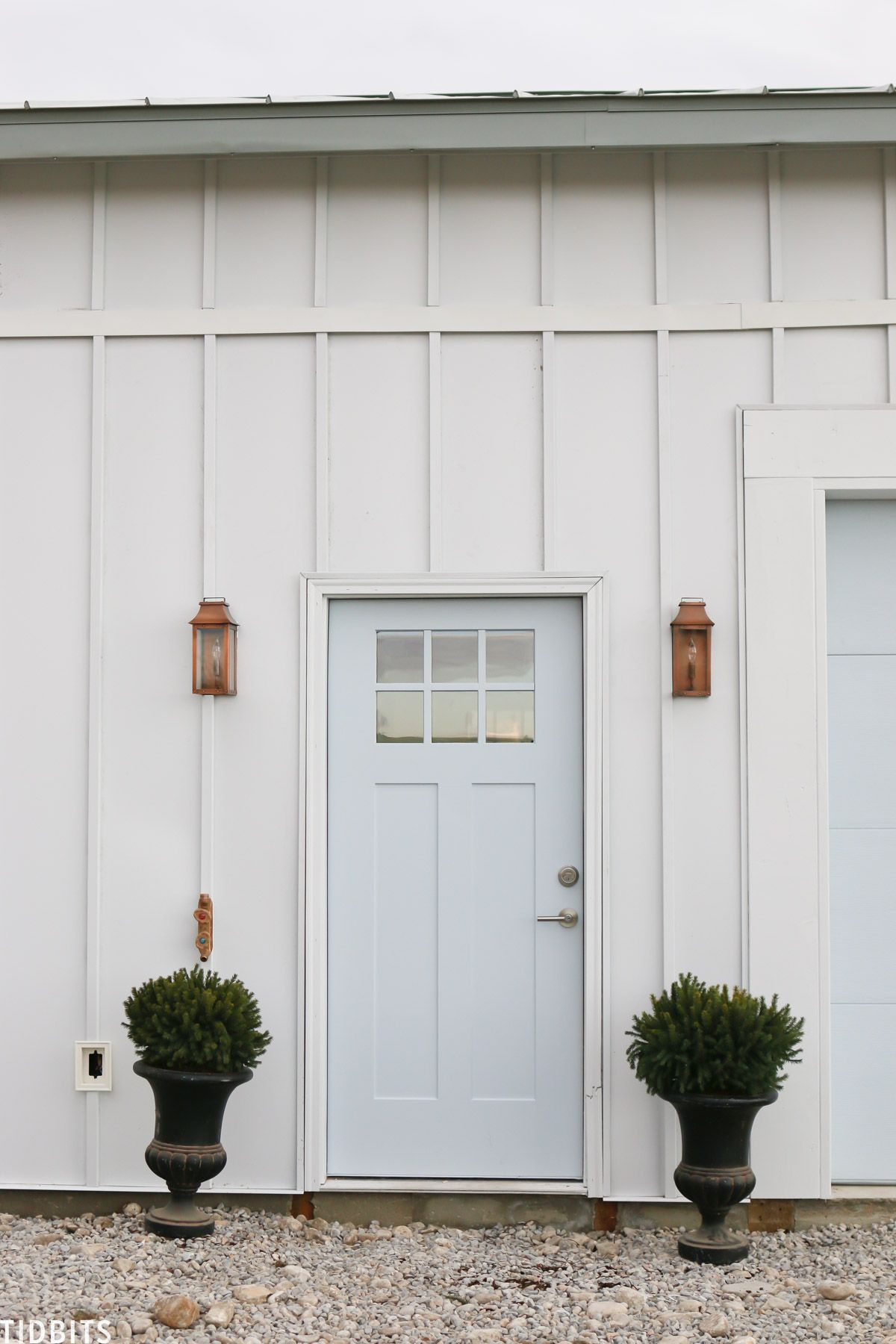 Garage Curb Appeal Design Ideas. It was time to add some garage curb appeal to our new pole barn home. In this process post, we've added our steel siding, steel roofing, painted our garage doors, added light fixtures and more. Let me show you! #garagedesign #garage #curbappeal #garagecurbappeal #camitidbits #homeexterior #steelsiding #steelroofing