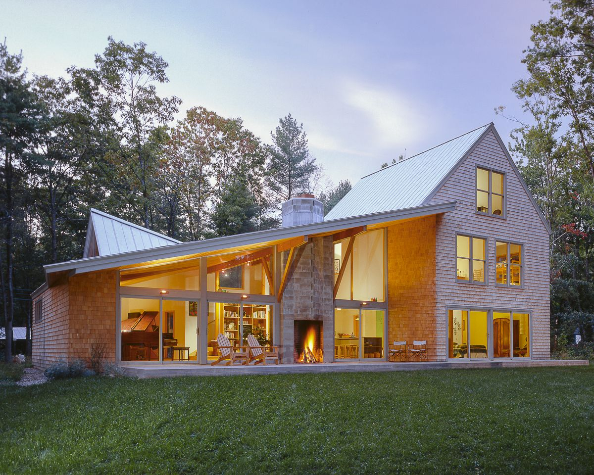 while the front of this house in falmouth  maine is traditional  large glass walls give a modern