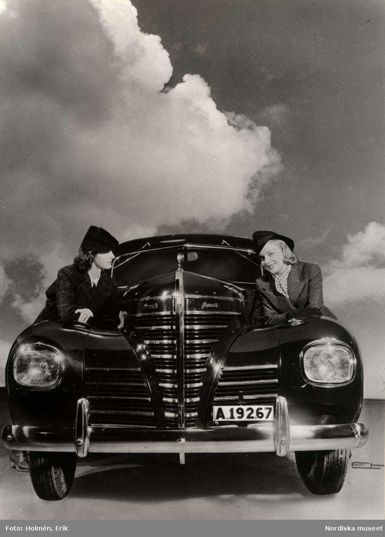 Två kvinnor i tweeddräkt och hatt lutar sig mot en bil av märket Plymouth 8670216072c98
