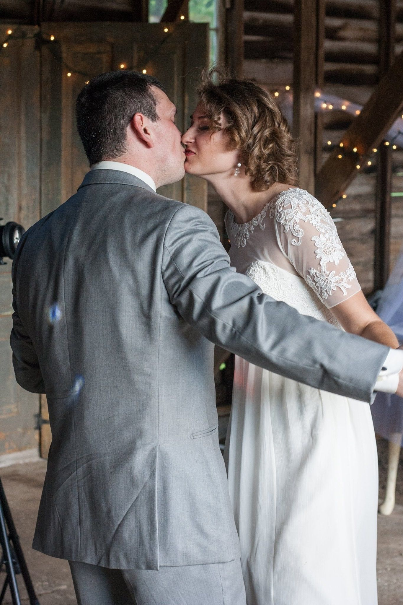 First dance wedding photo with bride and groom kissing. Rustic barn ...
