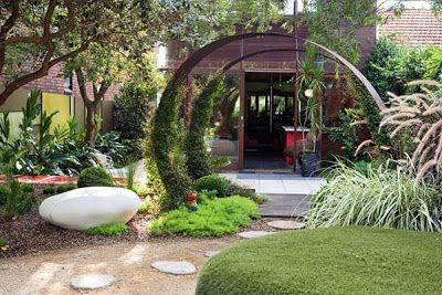 Jardin peque o con sendero de piedras y decoraci n en arco for Decoracion de jardines con piedras y madera