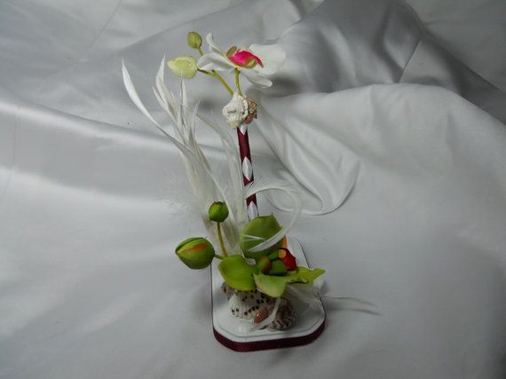 Suprise your guests in style with this signature wedding day guestbook pen with base!  This pen is wrapped in white ribbon, then criss crosses with maroon ribbon.  Atop sits a white orchid with buds behind it. Circled at the base of the flower is strategically placed seashells.  And to display your lovely pen is a 3x5 white painted wood base that your pen fits snugly in.  This base is wrapped at the bottom with maroon ribbon, and atop sits lovely seashells, lots of white feathers, a single…