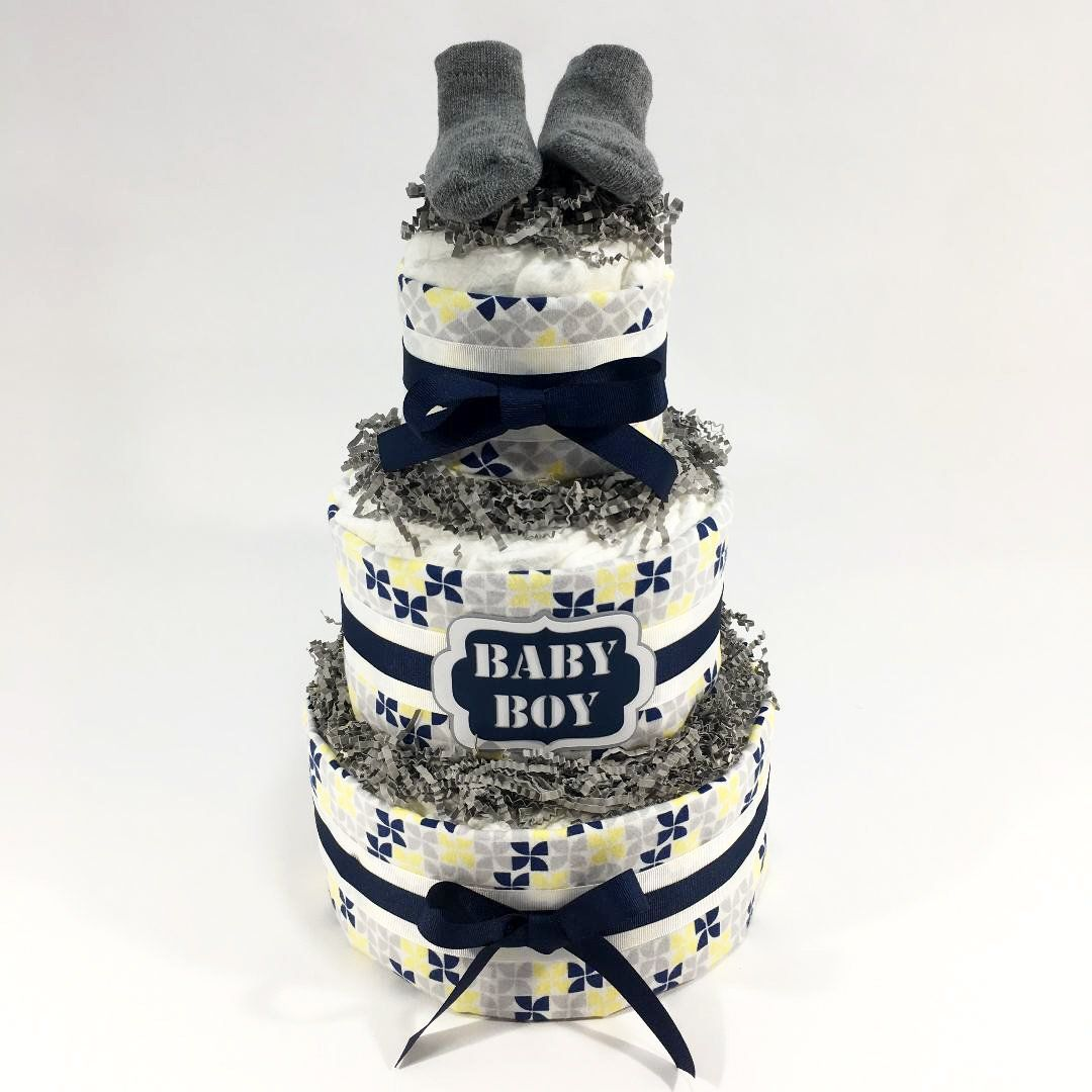 Navy, Yellow, Gray Boy Diaper Cake Centerpiece is part of Yellow Clothes Gray - Navy, gray, and yellow boy diaper cake centerpiece can also be given as a gift  Boy diaper cake includes 50 size 1 diapers  It includes a baby blanket, burp cloth, and rag  The tag reads  Baby Boy  and the topper is a pair of baby socks  The 3tier diaper cake is about 9  wide and 15  tall