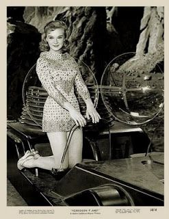 """Anne Francis poses with the Robby Jeep from """"Forbidden Planet""""."""