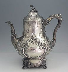 Eoff and Sheppard Coin Silver Teapot  An antique coin silver teapot by Eoff and Sheppard for Ball Black and Co of New York. Hand chased decoration of leaves and scrolls and a naturalistic handle and spout. The lid hinges to open. Monogrammed on one side in the cartouche. Circa 1860.