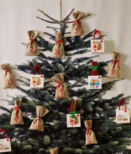 Bild einer Wohnzimmerwand, an der ein Wandbehang aus VINTER 2014 Meterware mit Weihnachtsbaummotiv hängt. Daran angebracht sind kleine Stoff- und Papierbeutel. Auf den Beuteln befinden sich Zahlen von 1-24 und um den Wandbehang hängt eine LED-Lichterkette.