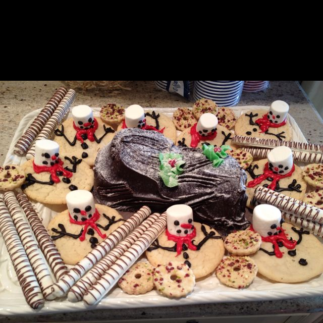Yummy Christmas treats! Chocolate Yule log, melting snowmen sugar cookies, white chocolate covered pretzel barks and cranberry & pistachio wreath cookies.